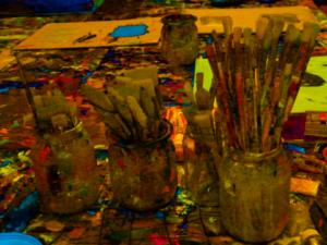 Gläser mit mehreren Farbpinseln auf einem Arbeitstisch.