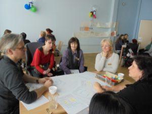 Personen am Tisch in einer Diskussion.