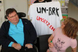 Zwei Teilnehmende am Aktions-Tag. Auf dem T-Shirt steht: UN-BRK umsetzen.