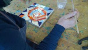 Eine Person legt bunte Steine zu einem Mosaik.