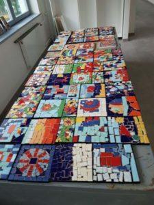 Auf einem Tisch liegen viele fertige Mosaike.