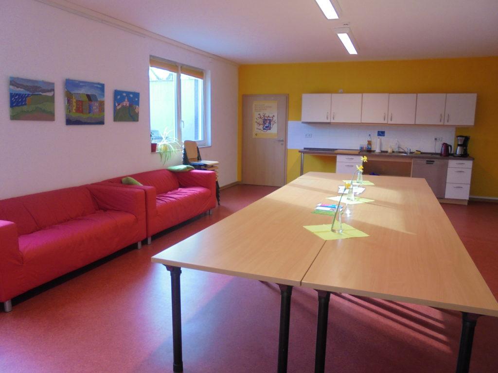 Großer Raum mit langer Tischreihe in der Mitte, einer Küche am Ende des Raumes und zwei Sofas am Rand.