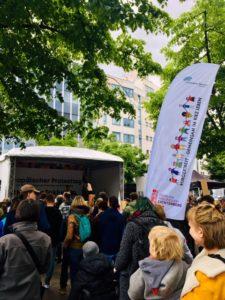 Foto von der Kundgebung. Vor einer überdachten Bühne stehen viele Menschen mit Blick zur Bühne.