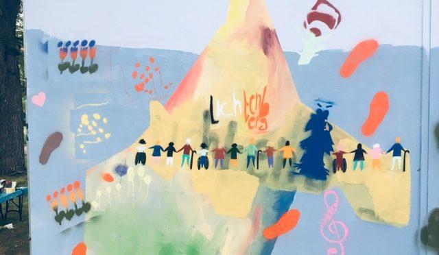 Ein Ausschnitt einer andere Wand, mit bunten Blumen, Fußstapgen und einer sehr diversen Menschenkette.