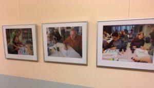 Drei Bilderrahmen mit Fotos der Ausstellung hängen an einer Wand.