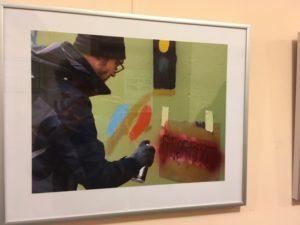 Ein gerahmtes Foto mit einem Mann, der mit Hilfe einer Schablone etwas an das Trafo-Häuschen sprüht.