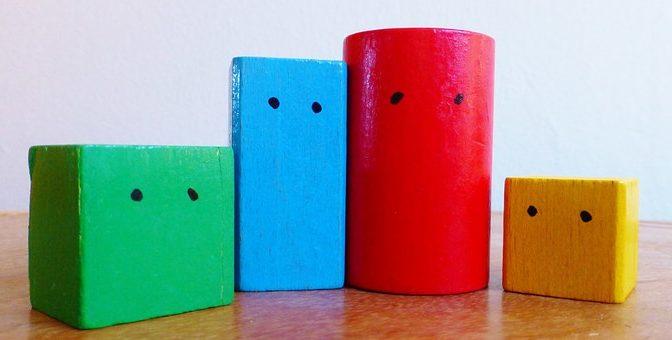 Bunte KLötze unterschiedlicher Form und Farbe mit auf´gemalten Augen, nebeneinander gestellt.