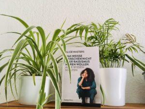 Foto vom Buch zwischen zwei Grünlilien.