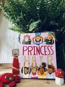 Foto vom Kinderbuch: Princess hair. vor einer grünen Pflanze, mit kleinem roten Holzfigürchen