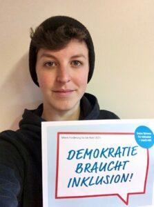 Amélie Sarramagnan mit Schild: Demokratie braucht Inklusion