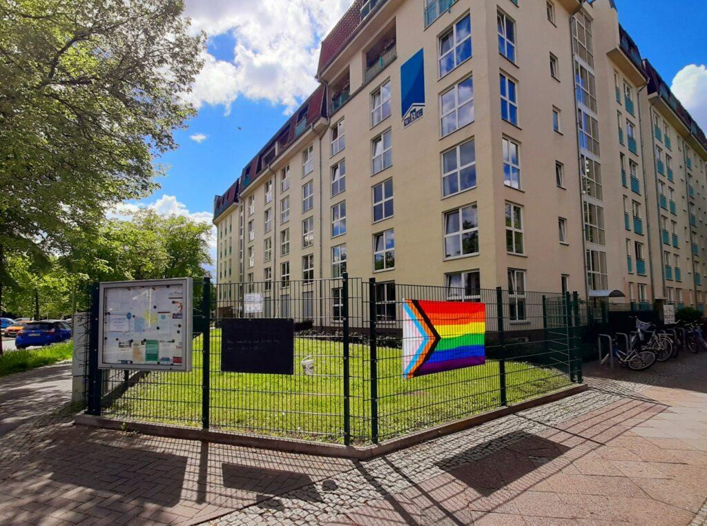 Zaun mit Fragetafel und Regenbogenflagge