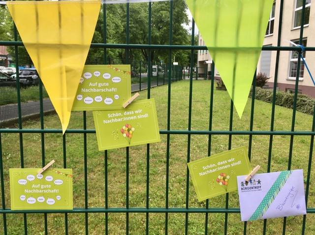 Postkarten zum Tag der Nachbarschaft mit Klammern an den Zaun geklemmt