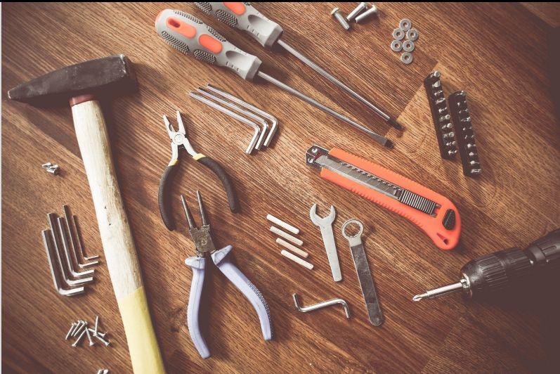 Verschiedenes Werkzeug auf Holztisch ausgebreitet